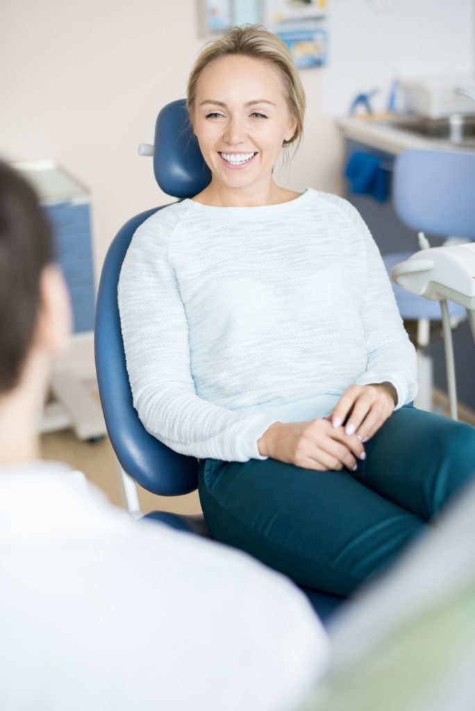 Cheerful woman in chair of dentist